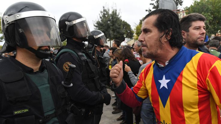 SANT JULIA DE RAMIS, SPAIN - OCTOBER 01: A man dressed in the Catalonian flag confronts officers as police move in on the crowds as members of the public gather outside to prevent them from stopping the opening and intended voting in the referendum at a polling station where the Catalonia President Carles Puigdemont will vote later today on October 1, 2017 in Sant Julia de Ramis, Spain. More than five million eligible Catalan voters are estimated to visit 2,315 polling stations today for Catalonia's referendum on independence from Spain. The Spanish government in Madrid has declared the vote illegal and undemocratic. (Photo by David Ramos/Getty Images)